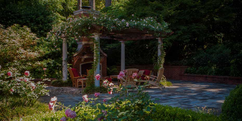A rose pergola covers a sitting area for outdoor entertaining